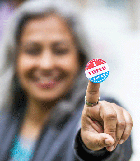 Voting sticker help up by a smiling person