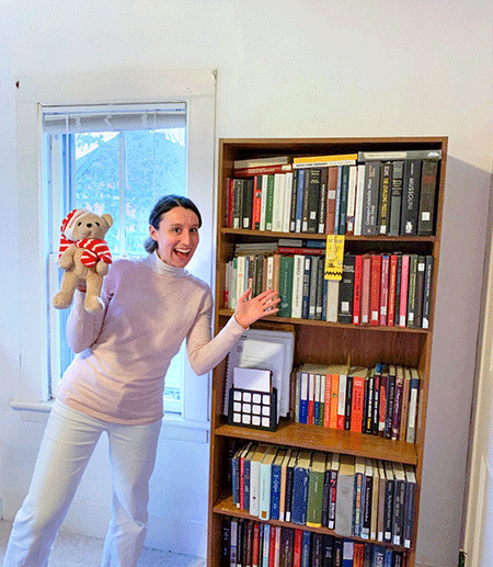 A graduate student smiles in front of all her books