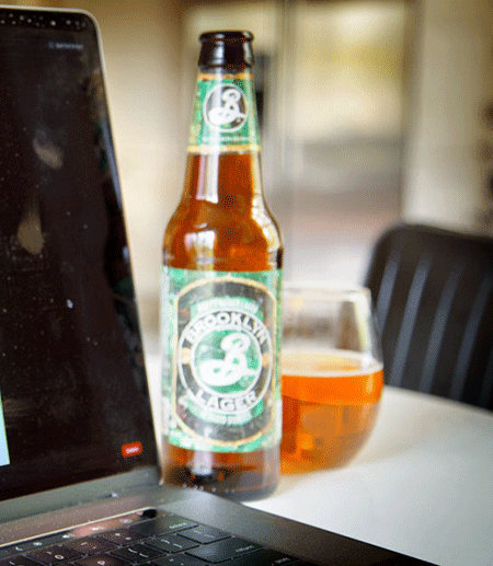 Beer bottle and glass by a computer