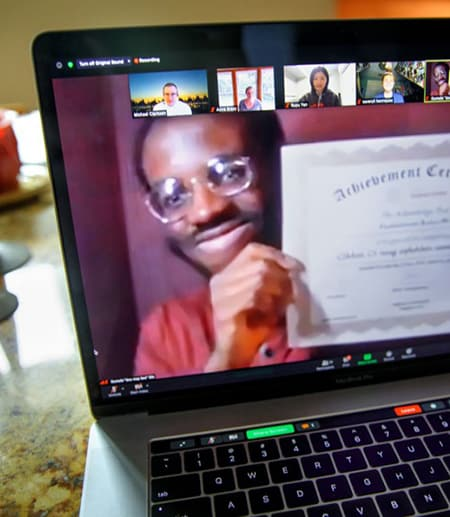 Person on computer screen, holding up a certificate