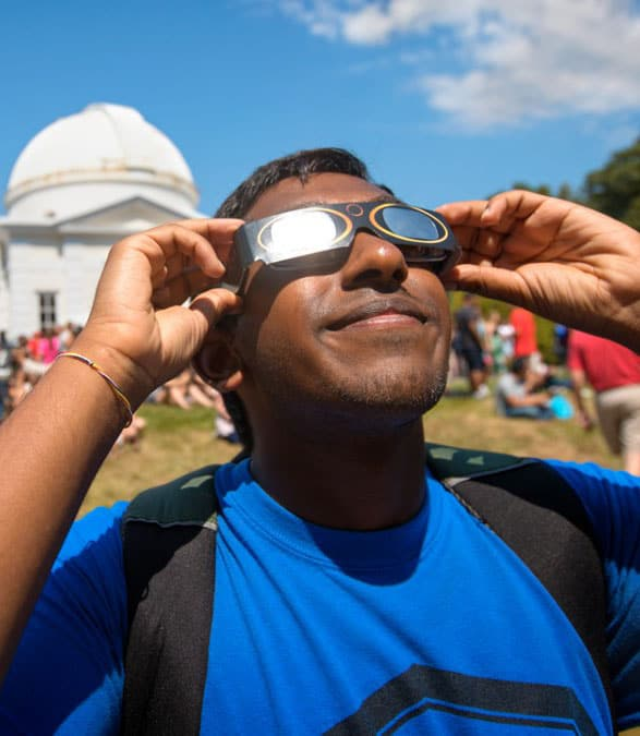 Student observing solar eclipse with special glasses