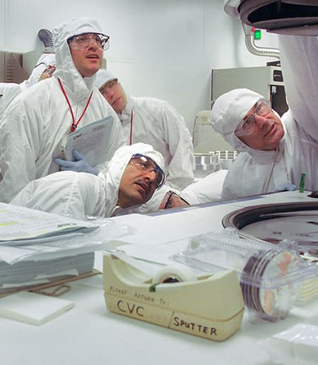 People in white protective gear and goggles, in a lab