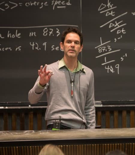 Professor giving lecture in-front of chalkboard with equations