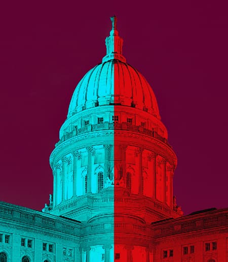The top of the U.S. Capitol building, half in blue and half in red