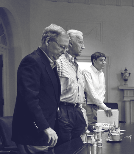Three men stand at a table