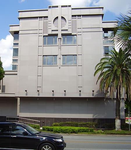 Grey concrete building, palm trees, blue sky