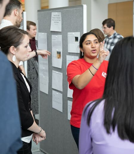 Swathi Chandrika '21 explains her group's project, building an experiment to predict the behavior of a mass on a spring when released at different positions and with different masses.