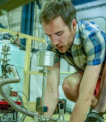 Brad Ramshaw kneeling by the magnet used in the experiment