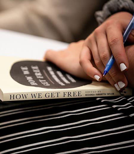 "The book ""How We Get Free"" on someone's lap"