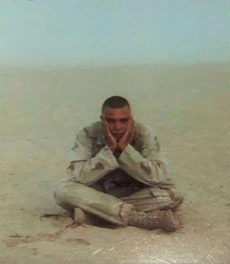 Marine soldier sitting cross-legged in the desert.