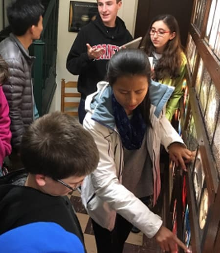 A group of students observe an object on the floor