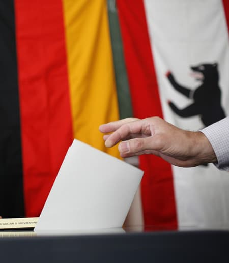 Hand placing ballot in a box