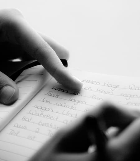 woman's hands writing in a notebook