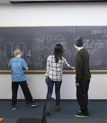 High school kids work at a chalkboard