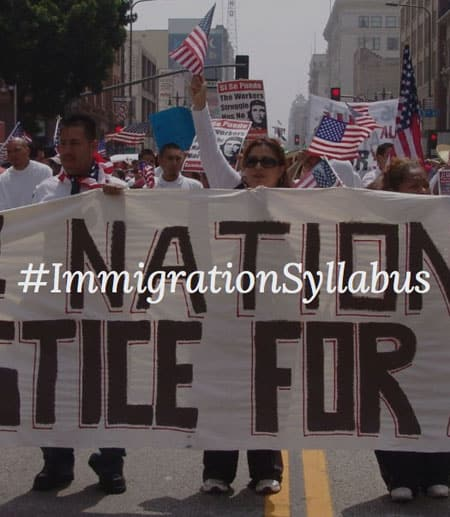 "Protesters holding banner saying ""Immigration Syllabus"""