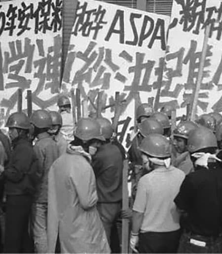 Japanese with helmets on in front of a  protest sign in Japanese