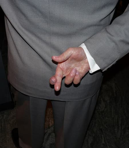 Man in business suit holding crossed fingers behind his back