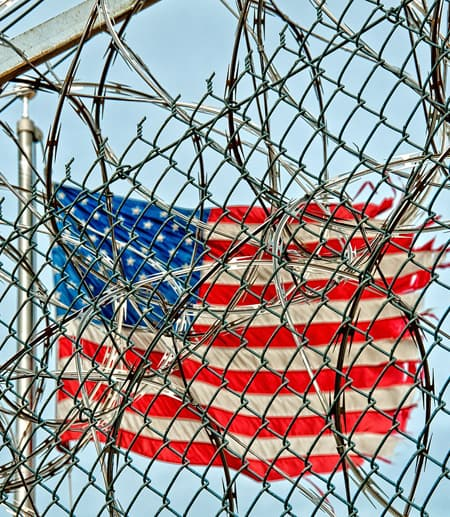 American flag through barbed wire