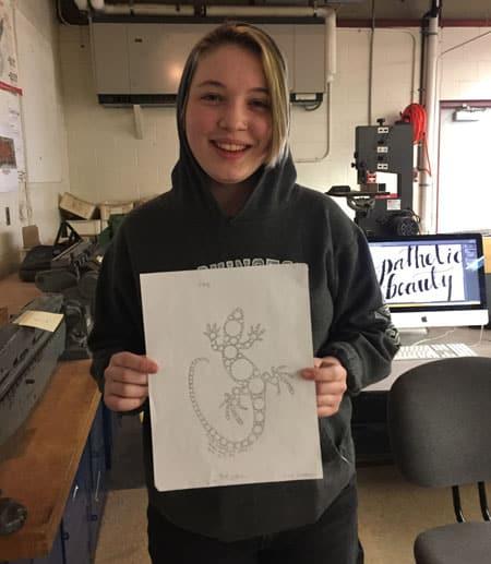 Olivia Lowman, winner of contest, holds up winning gecko design