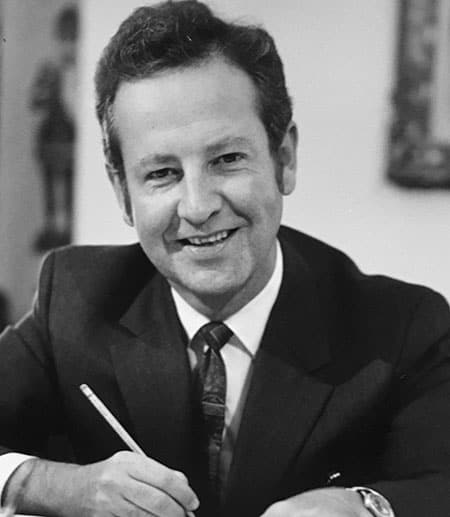 Robert Plane smiling, holding a pencil