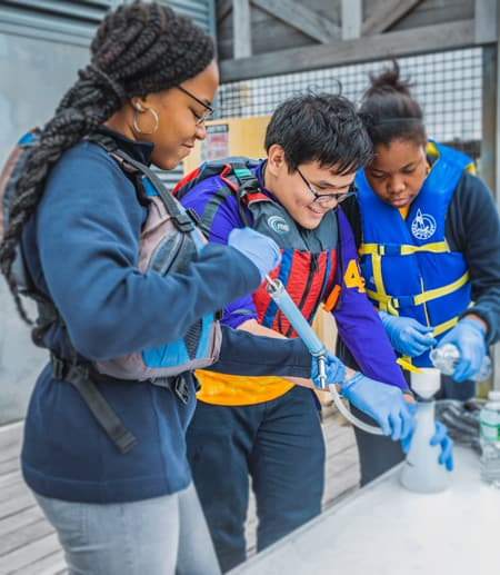 Students from Loughlin Memorial High School in New York City sample water from the Hudson River to help identify invasive species for the FishTracker program.