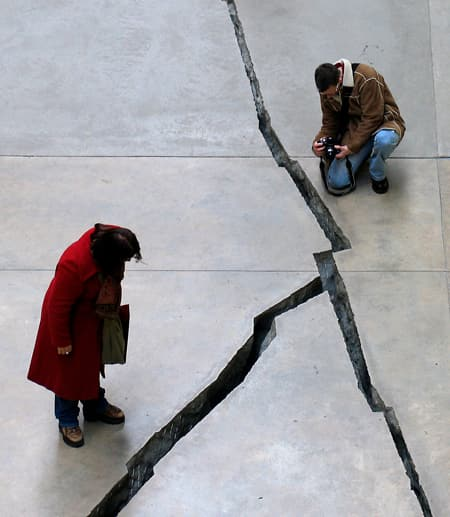A kneeling man and a standing woman gaze at a broad crack in the pavement