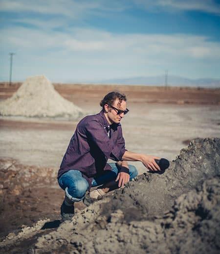 """Sam Harnett """"interviewing"""" a mud pot"""