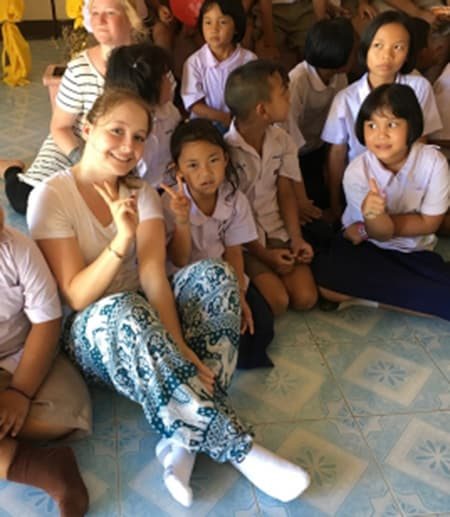 Sofia Aumann '19, center, spent part of her summer on a service trip to Thailand, where she studied the issue of sex trafficking. She also worked in this school in Chiang Rai where group members taught English lessons, danced, and played with the kids.