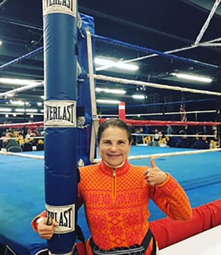 woman standing by boxing ring giving thumbs up