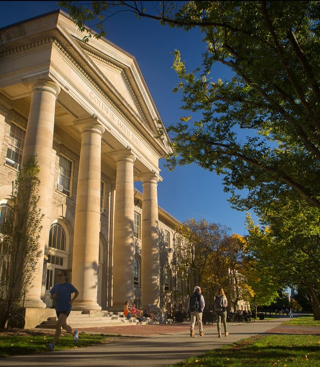 Students walk past Goldwin Smith Hall in the fall