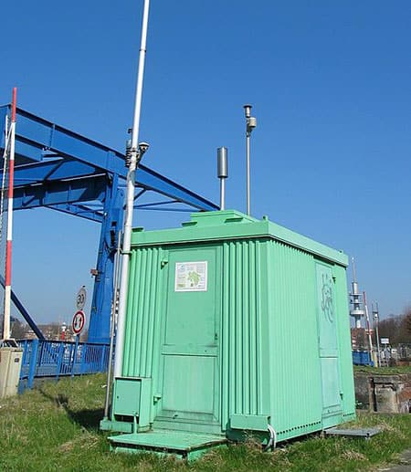 An air pollution measuring station, with a long pole rising above it to test the air.