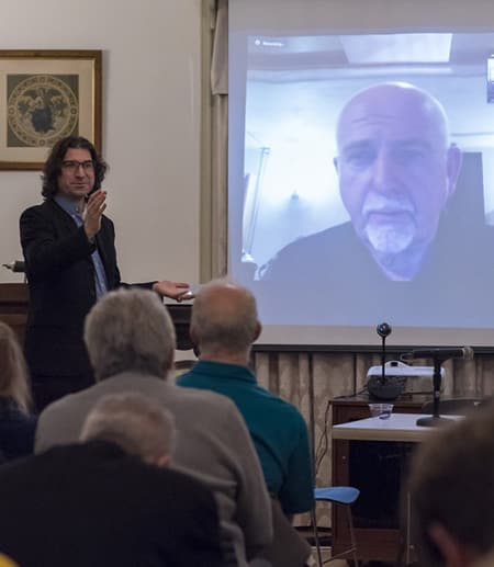 Professor Laurent Dubreuil chats with singer Peter Gabriel on screen.