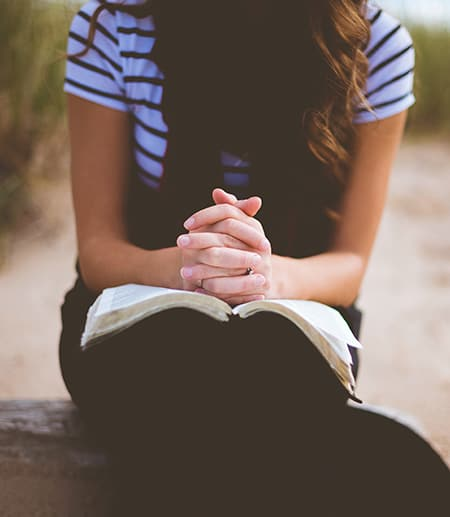 Hands folded on top of religious book