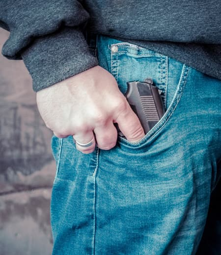 Hand touching gun in jeans pocket