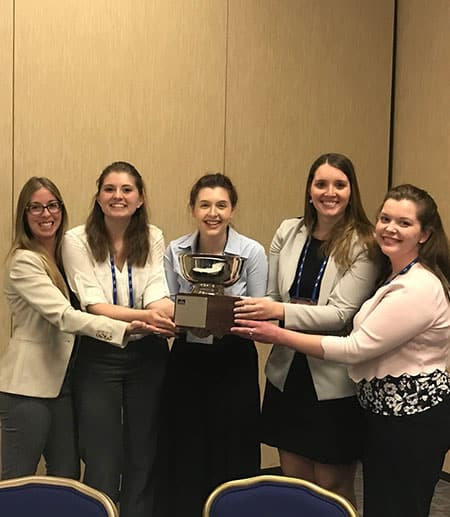 The four Ethics Bowl team members and Dana Randolph, each with one hand on the award bowl