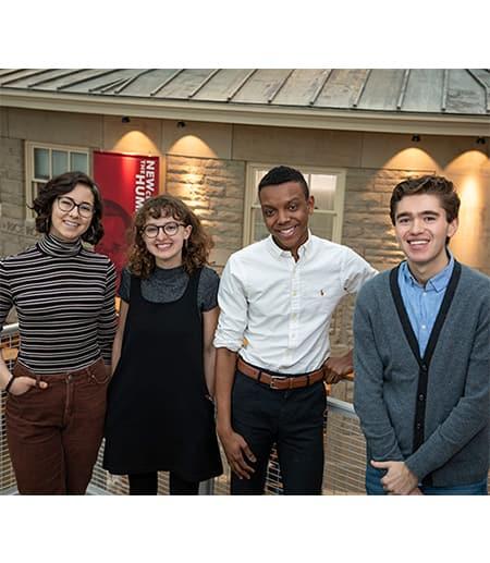 Four new college scholars stand in Klarman atrium