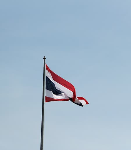 Flag of Thailand against a pale blue sky