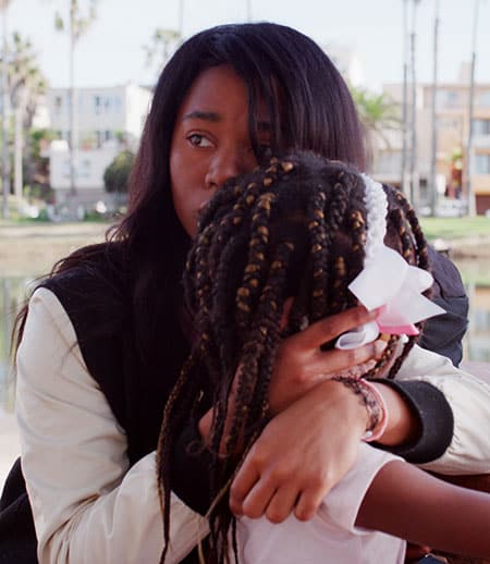 "Black woman hugging her daughter in a scene from ""From Land to Land"" film"