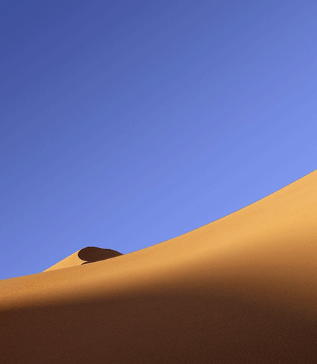 Sand dune under a blue sky