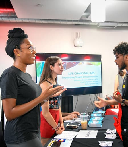 Students from Blackstone LaunchPad explain their resources during an entrepreneurship fair