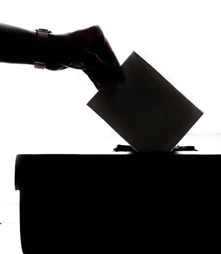 Silhouette of a hand putting a ballot on a box