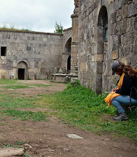 Person takes notes amidst old stone buildings