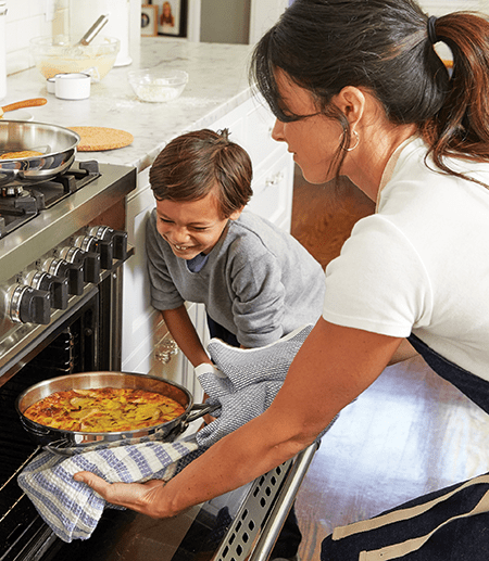 Mother and son placing food into an oven.