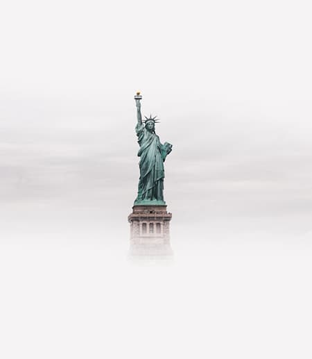 Statue of Liberty seen from a distance, surrounded by fog