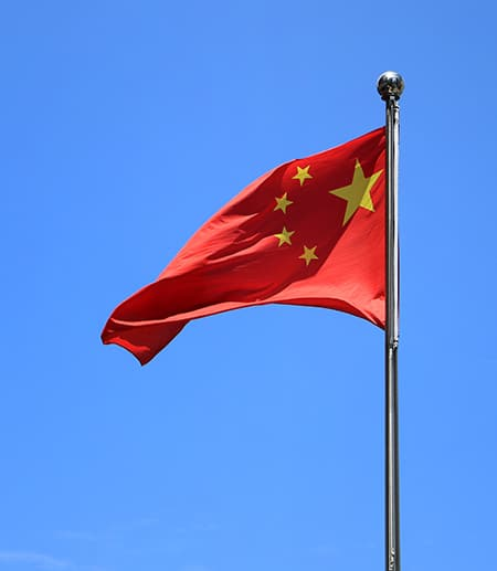 Red flag with yellow stars against a blue sky