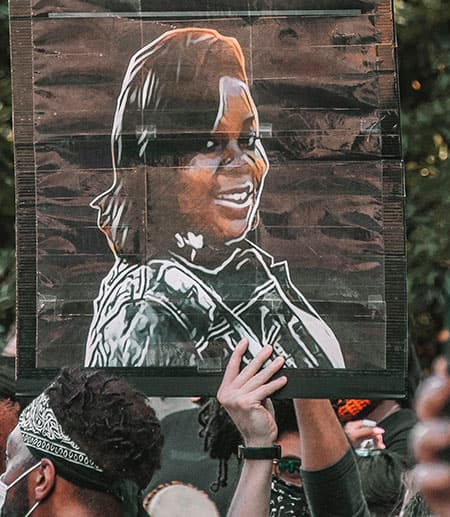 A poster with a drawing of Breonna Taylor carried aloft during a protest