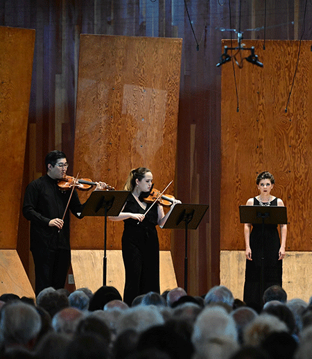 Three musicians perform on a stage