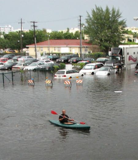 A person kayaking through floodwaters