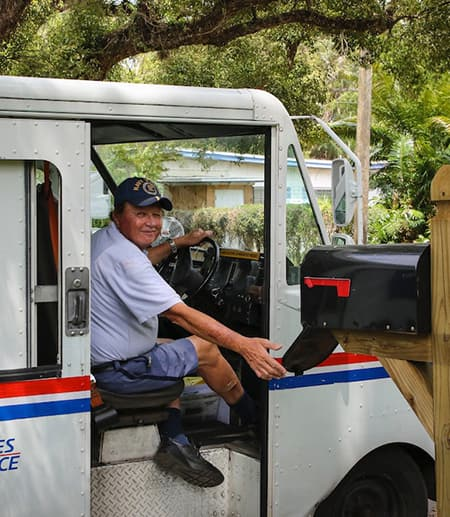 Person in blue uniform opening a mail box
