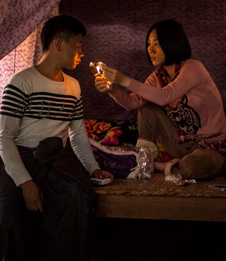 In an image from a Midi Z film, a woman offers a man a light for his cigarette